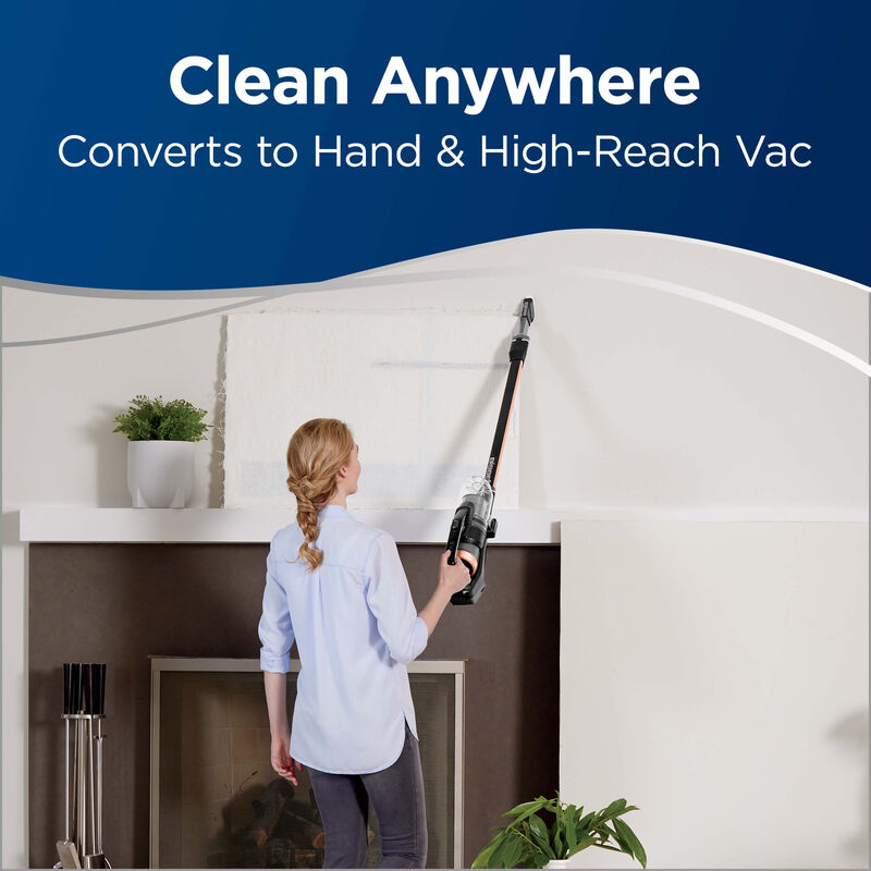 Using Extension Wand and Hand Vac to Clean Above Fireplace. Text: Clean Anywhere Converts to Hand and High-Reach Vac