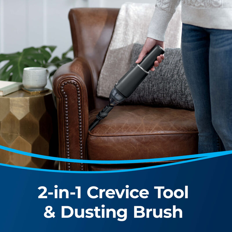 BISSELL AeroSlim Hand Vacuum 29869 Image: Vacuuming Couch Crevices Text: 2-in-1 Crevice Tool & Dusting Brush