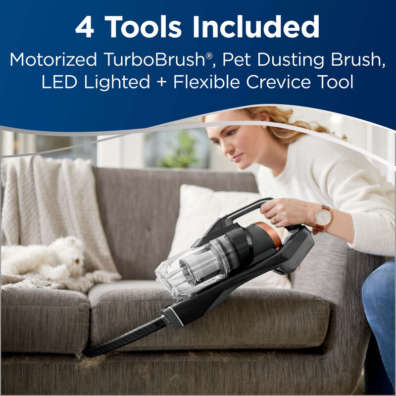 Using Crevice Tool with Hand Vac to Clean Couch Crevices. Text: 4 Tools Included: Motorized TurboBrush, Pet Dusting Brush, LED Lighted + Flexible Crevice Tool