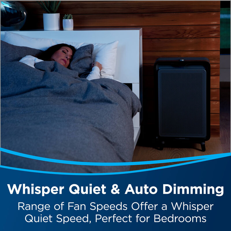air220 next to sleeping woman. Text: Whisper Quiet and Auto Dimming. Range of fan speeds offer a whisper quiet speed, perfect for bedrooms.